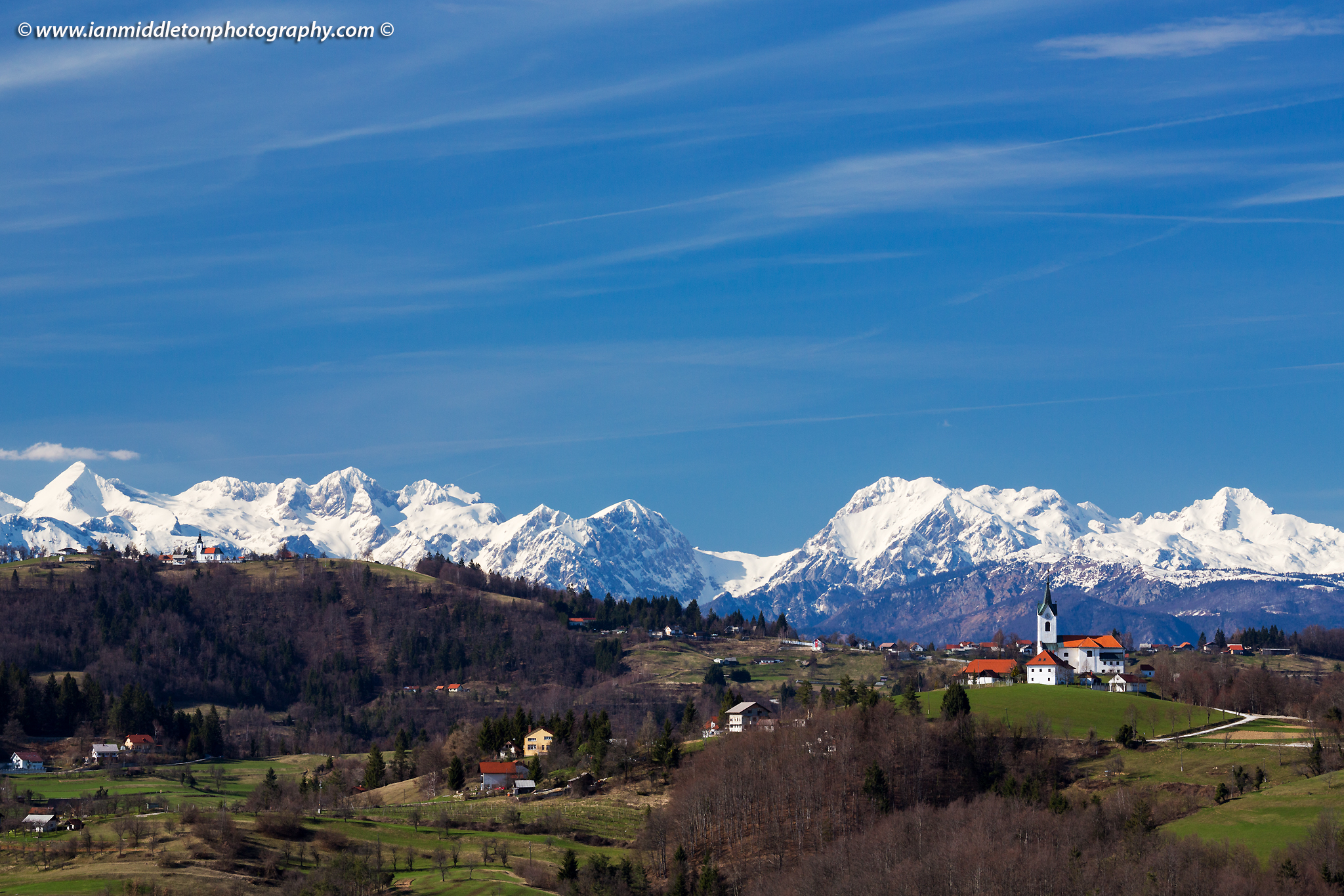 View across to the church of Saint Marjeta in Prezganje and church of Saint Nicholas in the Jance hills to the east of Ljubljana, Slovenia. The snow covered Kamnik Alps form a beautiful backdrop.