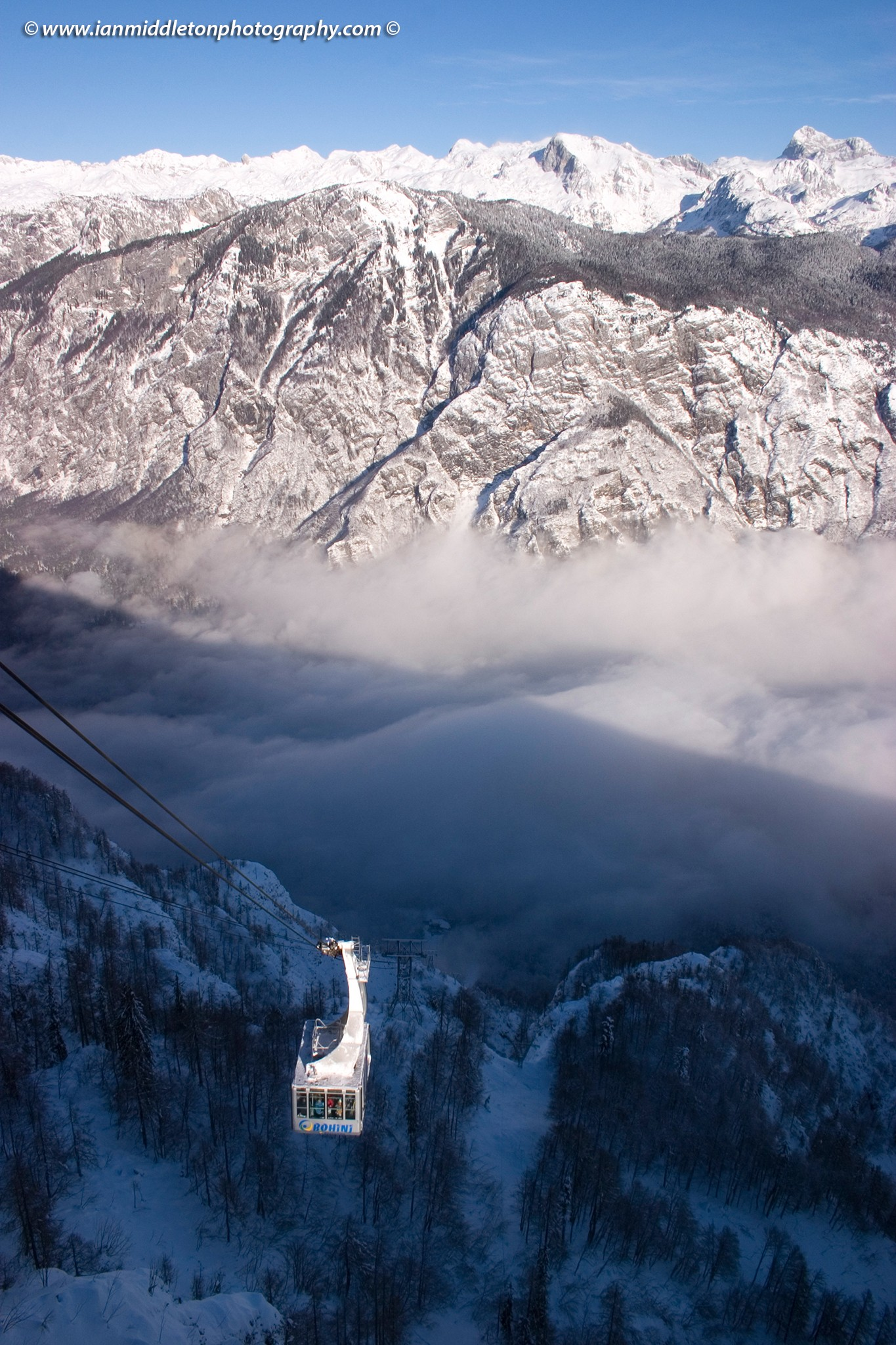 Winter view from Vogel Mountain as the cable car brings skiers up to the mountain, Slovenia. In the background you can see the snow covered Julian Alps and their highest mountain, Mount Triglav, covered in snow. The morning mist fills the valley.