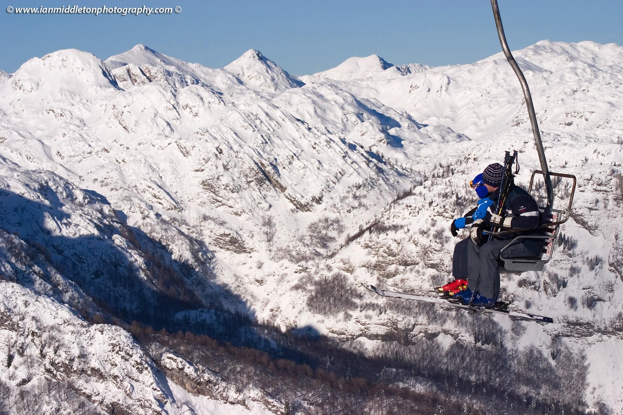 Skiers on chairlift at Vogel Ski resort in Slovenia.