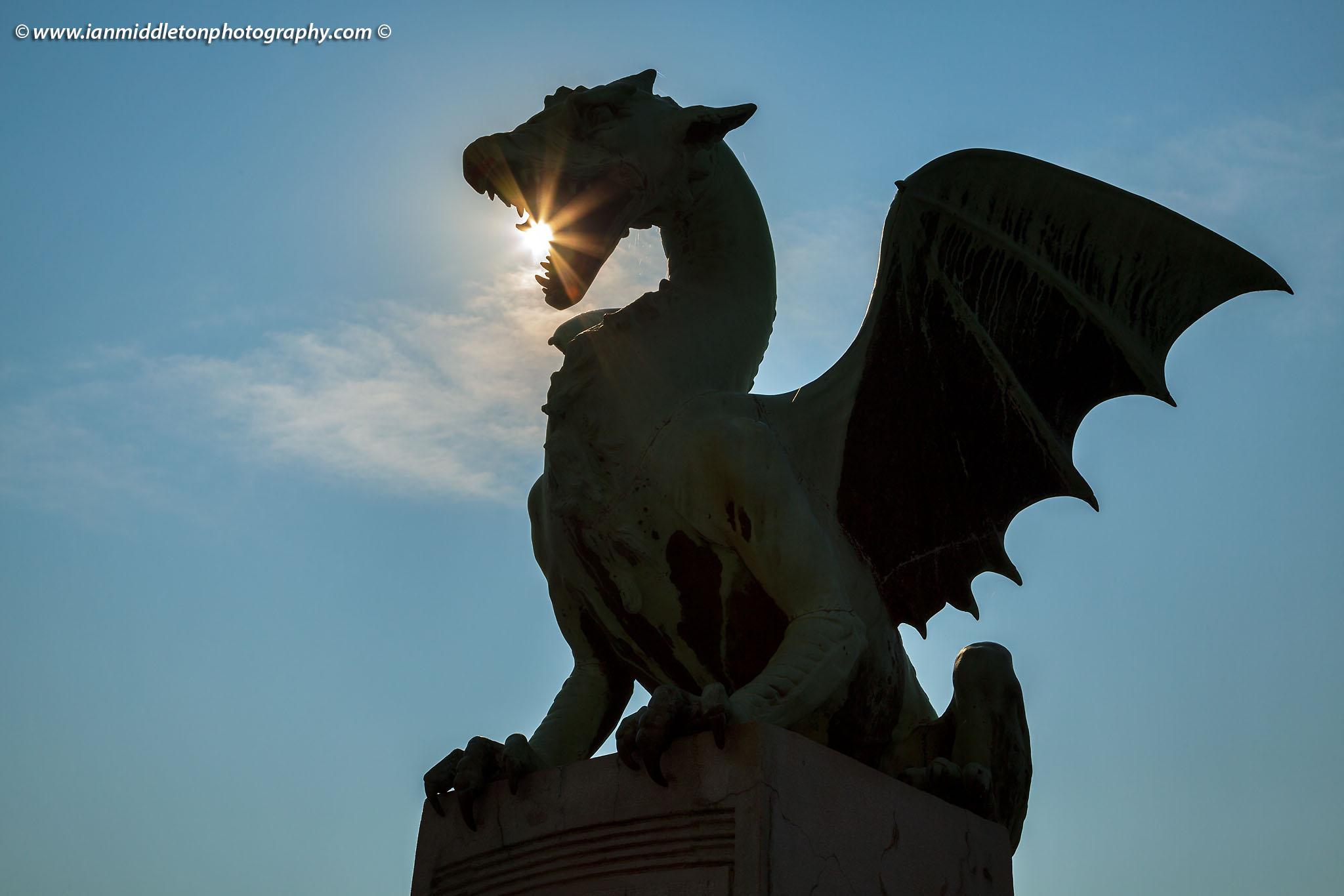 Sunburst through them mouth of a dragon on the Dragon Bridge in Ljubljana, Slovenia.