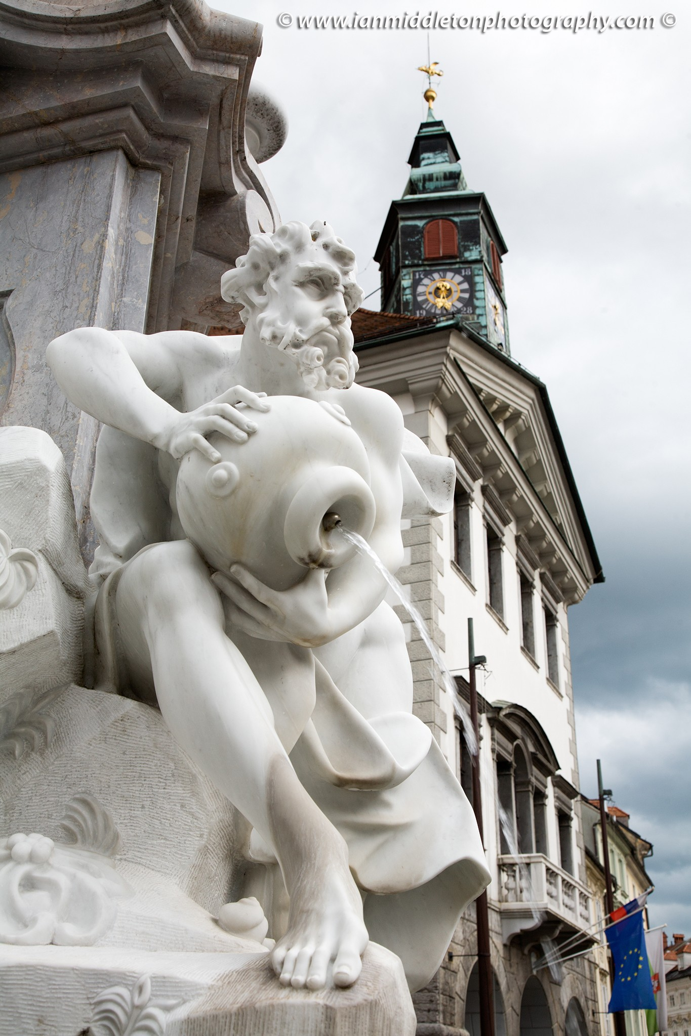 Robba Fountain, also known as the Fountain of Three Carniolan Rivers.It sits in the old town square (Mestni Trg) in front of the town hall. Built in 1751, this famous fountain is named after its creator, the Italian Baroque sculptor Francesco Robba (1698-1757). The pool is in the shape of a three leaf clover and from it rises a three sided obilisk. The fountain is adorned with the statues of the three river Gods: Krka, Ljubljanica and Sava, also the names of three of Slovenia's main rivers. The original has been removed and placed in a museum for protection, due to its fragile nature, and has been replaced with a replica. In the background is the city hall and the EU flag