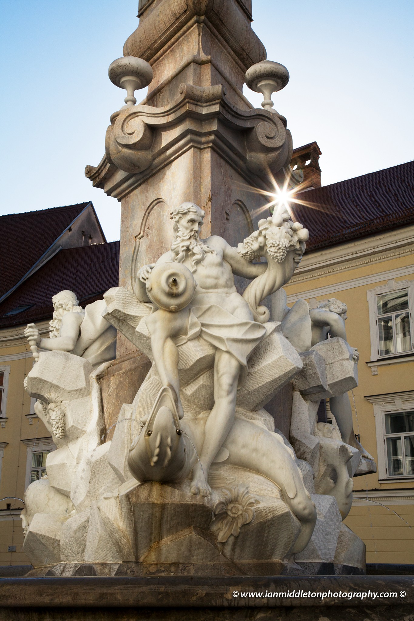 Backlit view of Robba Fountain, also known as the Fountain of Three Carniolan Rivers, with the sunburst from behind the tower. It sits in the old town square (Mestni Trg) in front of the town hall. Built in 1751, this famous fountain is named after its creator, the Italian Baroque sculptor Francesco Robba (1698-1757). The pool is in the shape of a three leaf clover and from it rises a three sided obilisk. The fountain is adorned with the statues of the three river Gods: Krka, Ljubljanica and Sava, also the names of three of Slovenia's main rivers. The original has been removed and placed in a museum for protection, due to its fragile nature, and has been replaced with a replica.
