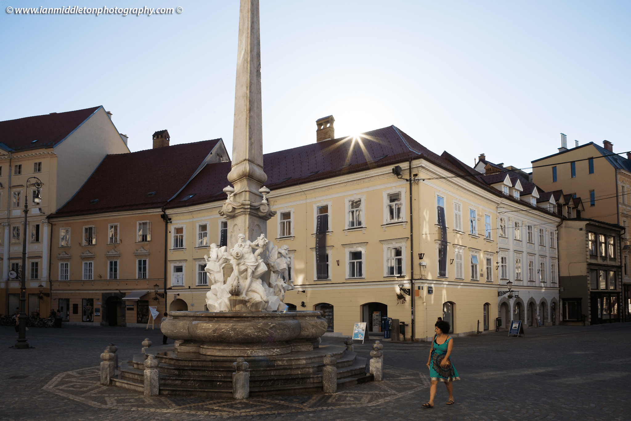 Backlit view of Robba Fountain and Mestni Trg, also known as the Fountain of Three Carniolan Rivers, with the sunburst from behind the tower. It sits in the old town square (Mestni Trg) in front of the town hall. Built in 1751, this famous fountain is named after its creator, the Italian Baroque sculptor Francesco Robba (1698-1757). The pool is in the shape of a three leaf clover and from it rises a three sided obilisk. The fountain is adorned with the statues of the three river Gods: Krka, Ljubljanica and Sava, also the names of three of Slovenia's main rivers. The original has been removed and placed in a museum for protection, due to its fragile nature, and has been replaced with a replica.