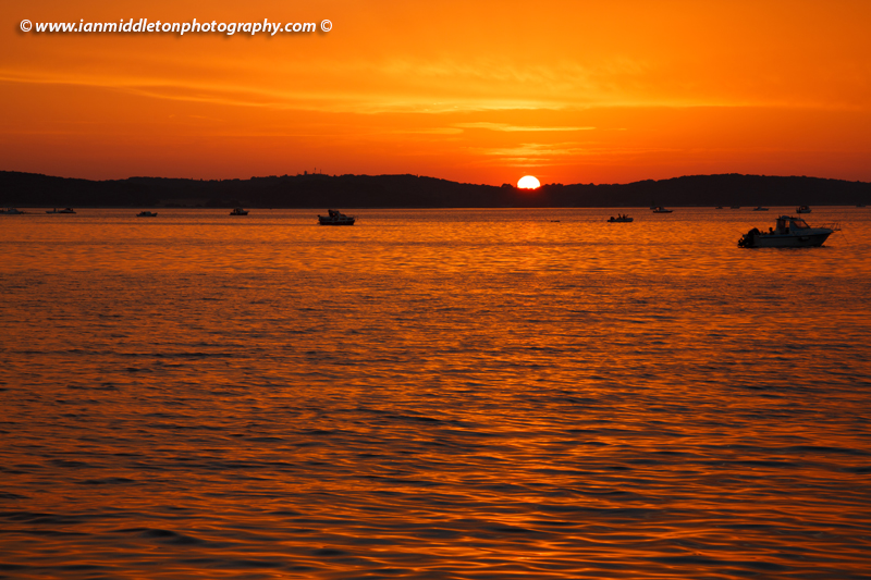 Fishing boats at sunset over the Brijuni Islands, Croatia. Seen from Puntižela Beach, Štinjan north of Pula.