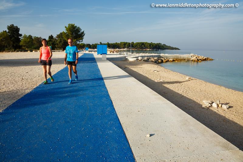 Couple taking an early morning stroll at Puntižela Beach, Štinjan north of Pula.