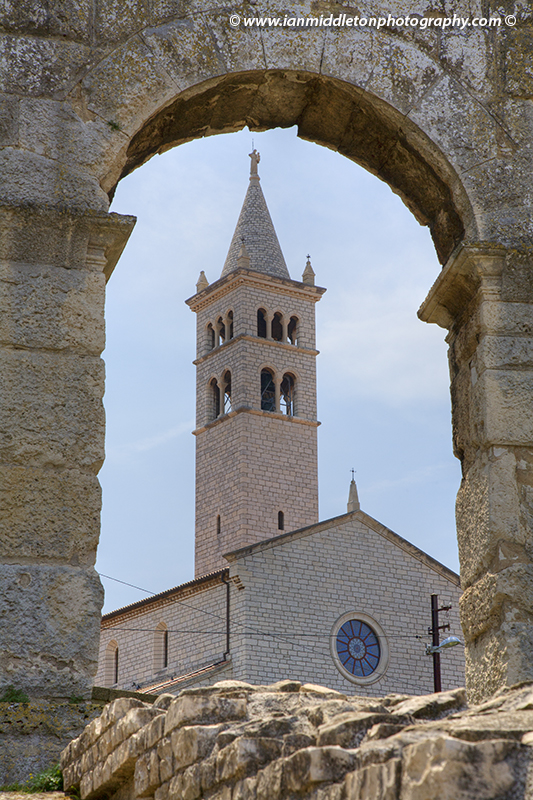 Church of St Anthony seen through archway of the Colosseum in pula, Croatia