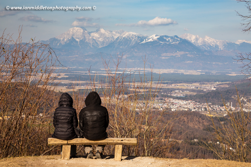 Couple on bench enjoying view from the church of Saint Jacob (Sveti Jakob) near Medvode, Slovenia. Situated on a hilltop in the Polhov Gradec Hill Range. This is also a popular hiking spot for locals.