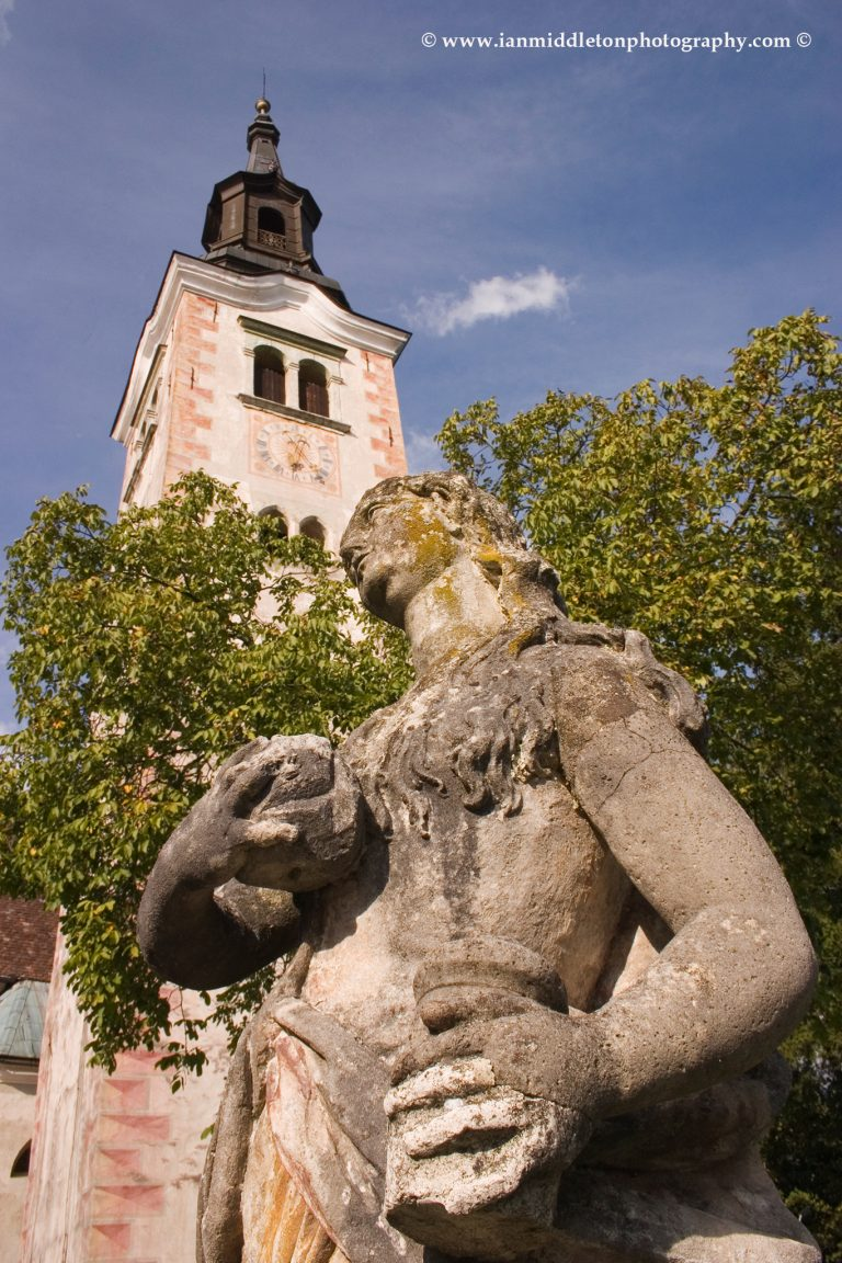 Statue of Mary Magdalene on Bled Island with the bell tower behind.